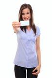 Donna abbastanza giovane che tiene un businesscard in bianco fotografia stock