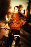 donna abbastanza giovane con la bicicletta in una strada di città fotografia stock libera da diritti