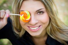 Donna abbastanza giovane con la copertura del lollypop il suo occhio Immagini Stock