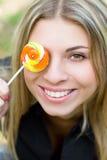 Donna abbastanza giovane con la copertura del lollypop il suo occhio Fotografia Stock