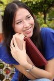 Donna abbastanza giovane del ritratto che tiene un libro Immagini Stock