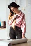 Donna abbastanza giovane dell'architetto che lavora all'i modelli nell'ufficio Immagine Stock