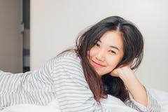 Donna abbastanza giovane dell'Asia che sorride e che esamina macchina fotografica Fotografia Stock