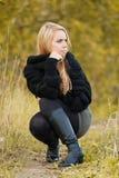 Donna abbastanza giovane in una sosta in giorno di autunno Fotografia Stock