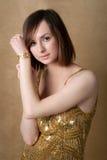 Donna abbastanza giovane in vestito dall'oro con la vigilanza di oro Immagini Stock Libere da Diritti