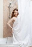 Donna abbastanza nuda che si nasconde dietro la tenda di doccia Immagini Stock