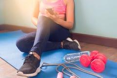 Donna in abbigliamento di forma fisica facendo uso dello smartphone, dello stile di vita sano e dell'allenamento Fotografie Stock Libere da Diritti