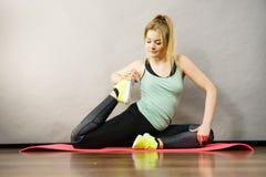 Donna in abiti sportivi che allungano le gambe Fotografie Stock