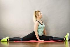 Donna in abiti sportivi che allungano le gambe che fanno cordicella Fotografia Stock