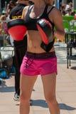 Donna in abiti sportivi che fanno forma fisica con i guanti mezzi di perforazione in all'aperto Fotografie Stock