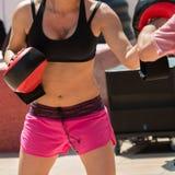 Donna in abiti sportivi che fanno forma fisica con i guanti mezzi di perforazione in all'aperto Immagini Stock Libere da Diritti