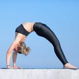 Donna in abiti sportivi che fanno ponte relativo alla ginnastica su aria aperta Fotografia Stock Libera da Diritti