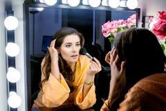 Donna in abito arancio che fa il suo trucco e che wathching in specchio Fotografia Stock Libera da Diritti
