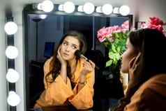 Donna in abito arancio che fa il suo trucco e che wathching in specchio Immagini Stock Libere da Diritti