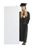 Donna in abito di graduazione che indica sul tabellone per le affissioni Fotografia Stock