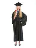 Donna in abito di graduazione che mostra diploma Immagine Stock