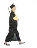 Donna in abito di graduazione con i libri che vanno lateralmente Fotografie Stock Libere da Diritti