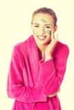 Donna in accappatoio rosa che ha maschera facciale Immagini Stock Libere da Diritti