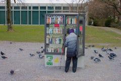 Donna ad un libro pubblico accantonare alla riva del lago di Biel/Bienne, Svizzera fotografia stock libera da diritti