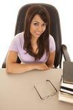 Donna ad uno scrittorio con una pila di angolo superiore dei libri Fotografie Stock