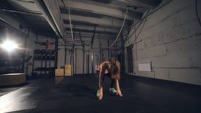 Donna adatta in abiti sportivi colourful che fanno i burpees su una stuoia di esercizio in un tipo industriale grungy spazio video d archivio