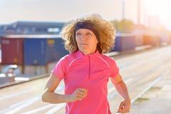 Donna adatta in buona salute che corre giù una via della città fotografia stock