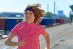 Donna adatta in buona salute che corre gi? una via della citt? immagine stock libera da diritti