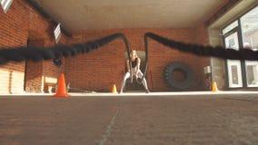 Donna adatta caucasica che si esercita con le corde di battaglia alla palestra stock footage