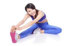 Donna adatta che allunga la sua gamba per riscaldare Fotografia Stock