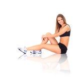 Donna adatta che allunga la sua gamba per riscaldare Fotografia Stock Libera da Diritti