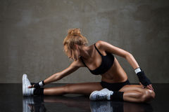 Donna adatta che allunga la sua gamba sopra fondo scuro Immagine Stock Libera da Diritti