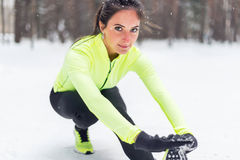Donna adatta che allunga scaldarsi prima dell'eseguire all'aperto allenamento di addestramento della via di inverno Immagine Stock