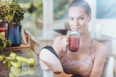 Donna adatta che beve frullato rosso immagini stock