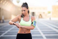 Donna adatta che cronometra la sua frequenza cardiaca con l'orologio immagini stock