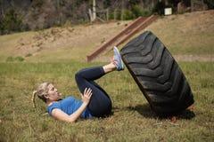 Donna adatta che esegue allenamento della gamba con la fila durante la corsa ad ostacoli Immagini Stock Libere da Diritti