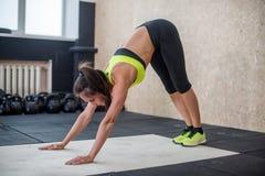 Donna adatta che esegue posa discendente del cane, facente yoga nella palestra Fotografia Stock Libera da Diritti