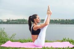 Donna adatta che esercita seduta sulle gambe di sollevamento della stuoia Fotografie Stock
