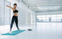 Donna adatta che esercita yoga nello studio di forma fisica Immagine Stock