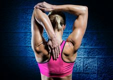 Donna adatta che fa allungando esercizio contro il fondo blu della parete Fotografia Stock