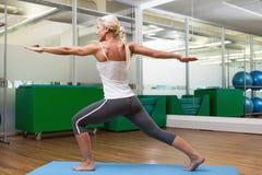 Donna adatta che fa allungando esercizio in palestra Fotografia Stock Libera da Diritti
