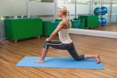 Donna adatta che fa allungando esercizio in palestra Immagine Stock