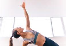 Donna adatta che fa la posa di yoga della sponda Immagini Stock