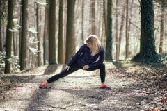 Donna adatta che fa yoga in foresta Fotografia Stock