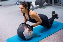 Donna adatta che si esercita con l'allenamento della palla medica Immagine Stock