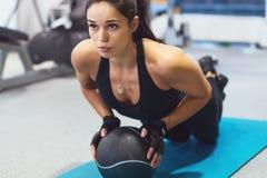 Donna adatta che si esercita con l'allenamento della palla medica fotografia stock libera da diritti