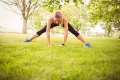 Donna adatta che si esercita con l'allungamento della gamba Fotografia Stock
