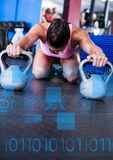 Donna adatta che si esercita di forma fisica facendo uso del kettlebell nella palestra con l'interfaccia di forma fisica Fotografie Stock Libere da Diritti