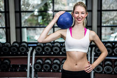 Donna adatta con la mano sulla palla medica della tenuta dell'anca Fotografia Stock Libera da Diritti