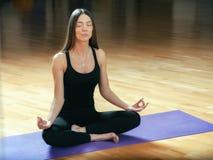 Donna adatta dei bei giovani che si siede nella posa di loto sulla stuoia di yoga Fotografia Stock Libera da Diritti