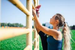 Donna adatta dei giovani in camicia blu e ghette che si prepara all'aperto al tramonto Donna di forma fisica che fa allungamento  Fotografie Stock Libere da Diritti